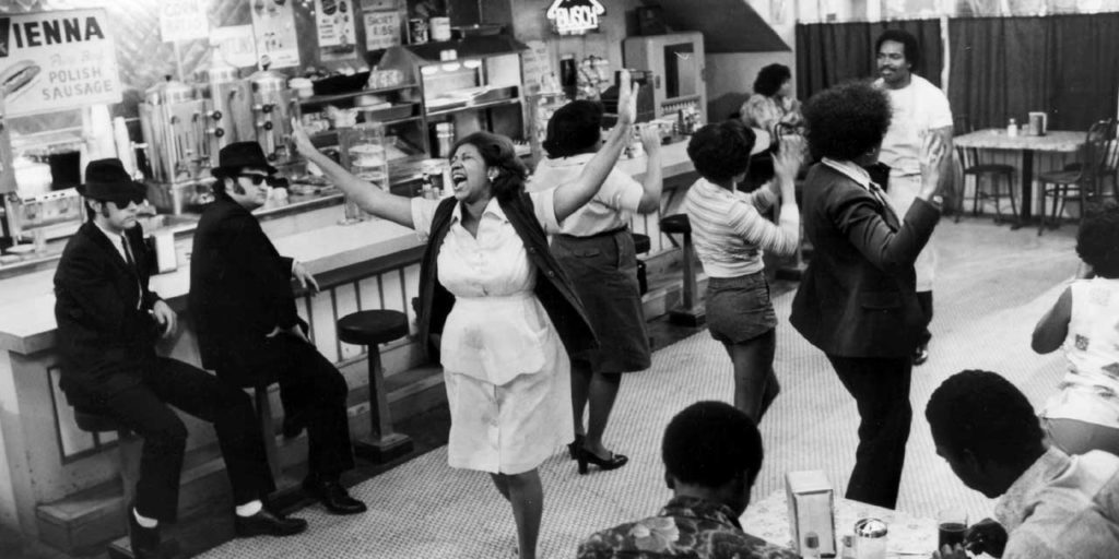 Aretha Franklin singing in a diner in The Blues Brothers. Image via City Journal